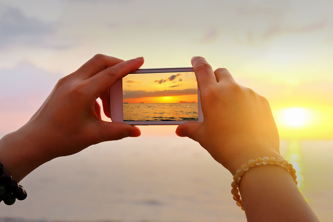 Hands holding iPhone taking photo of sunset